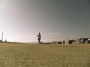 foto de mulher correndo na praia